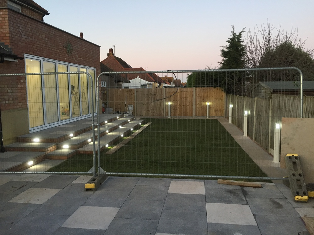 picture showing the rear of the house with the finished extension and landscaped garden, with the newly installed lights.