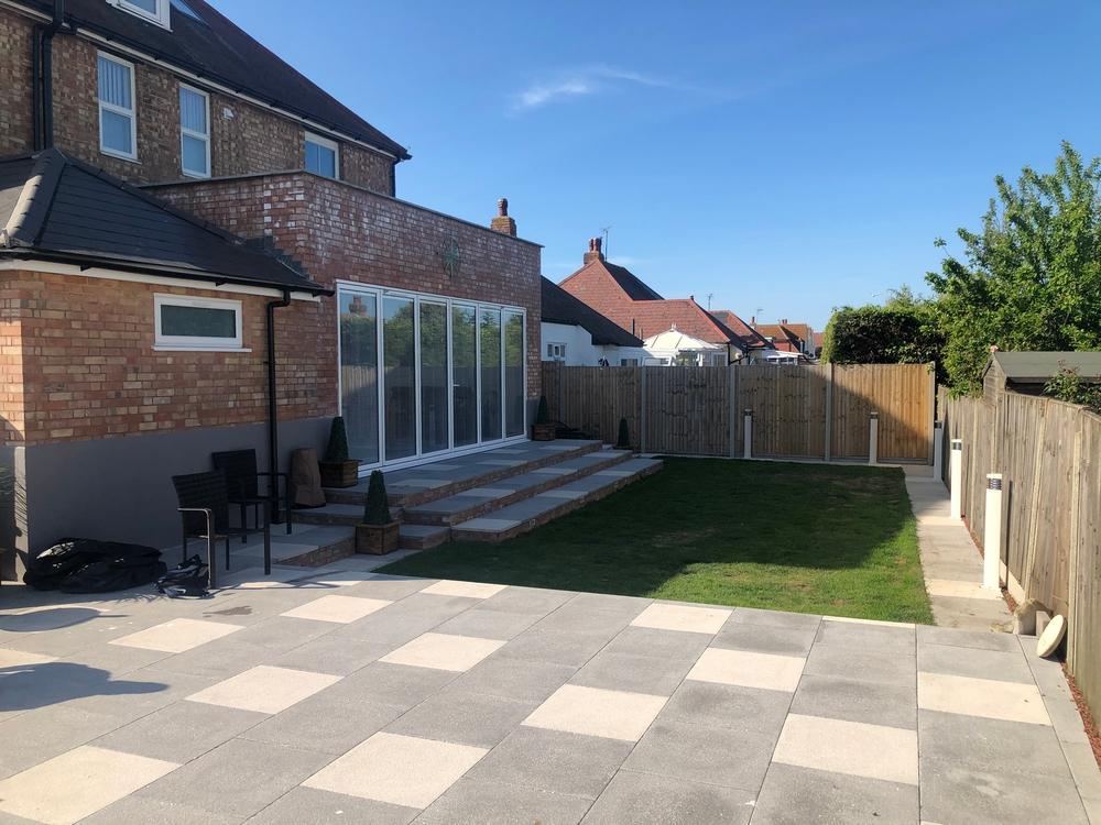 picture of a rear garden laid to lawn, a patio, steps onto the lawn and the finished extension